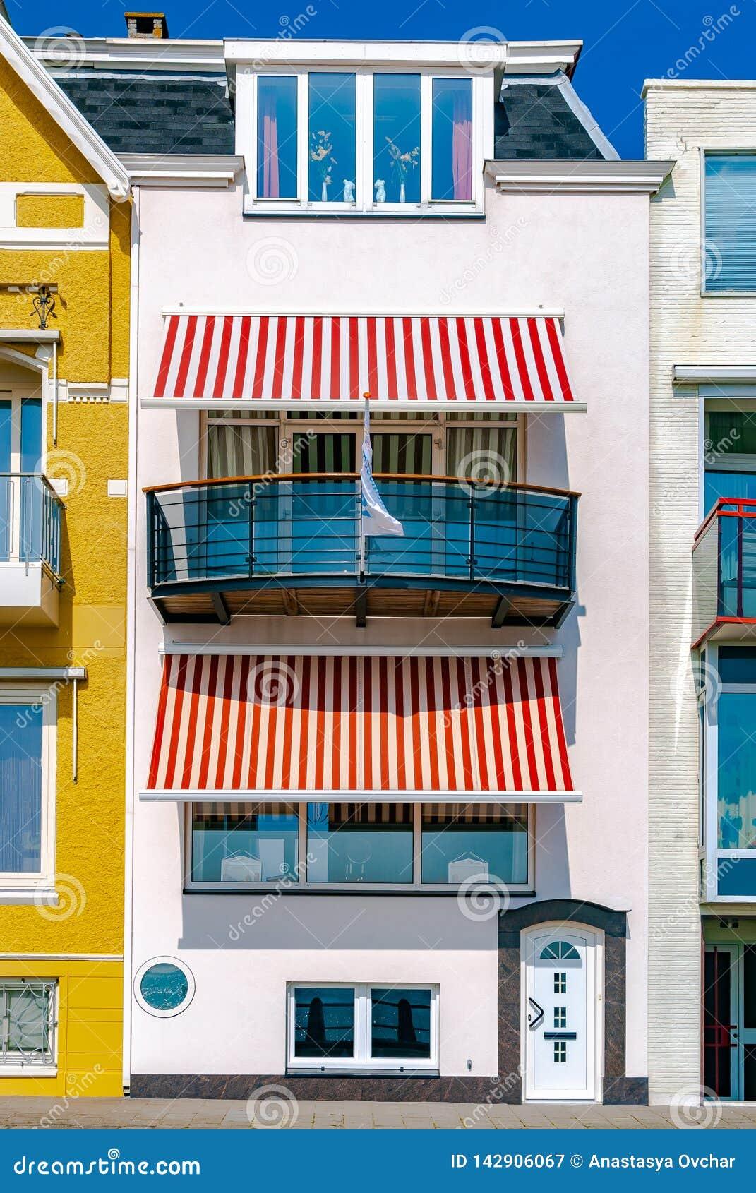 Una bella casa della localit? di soggiorno del mare bianco con i ciechi a strisce bianchi e rossi del sole Concetto di vacanza vi