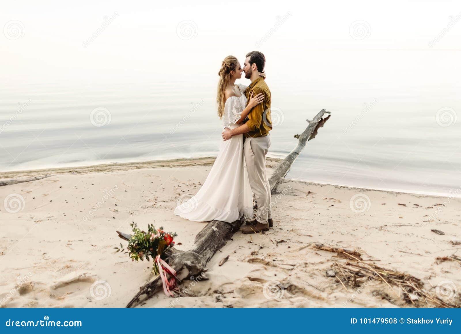 Una bella coppia sta abbracciando sui precedenti del mare Momento prima del bacio Data romantica sulla spiaggia nozze