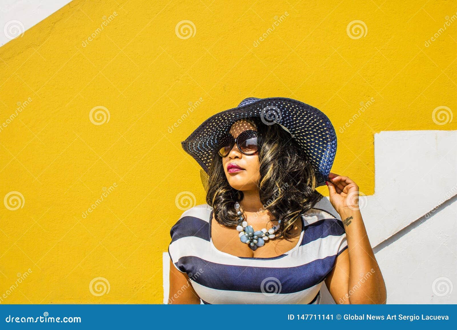 Una bella donna africana in un vestito a strisce blu e bianco che modella davanti ad una casa tradizionale BO-Kaap con le pareti