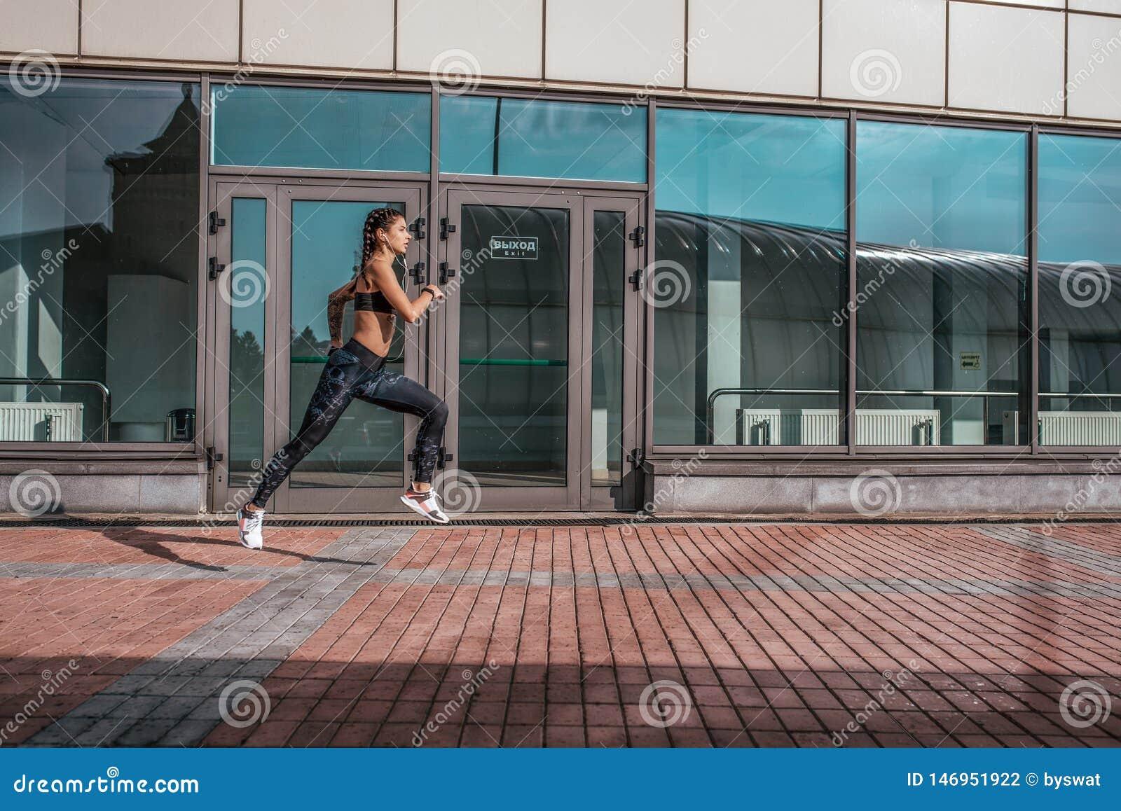 Una bella donna, una ragazza funziona di estate in città, su un trotto di mattina, pelle abbronzata Le ghette degli abiti sportiv