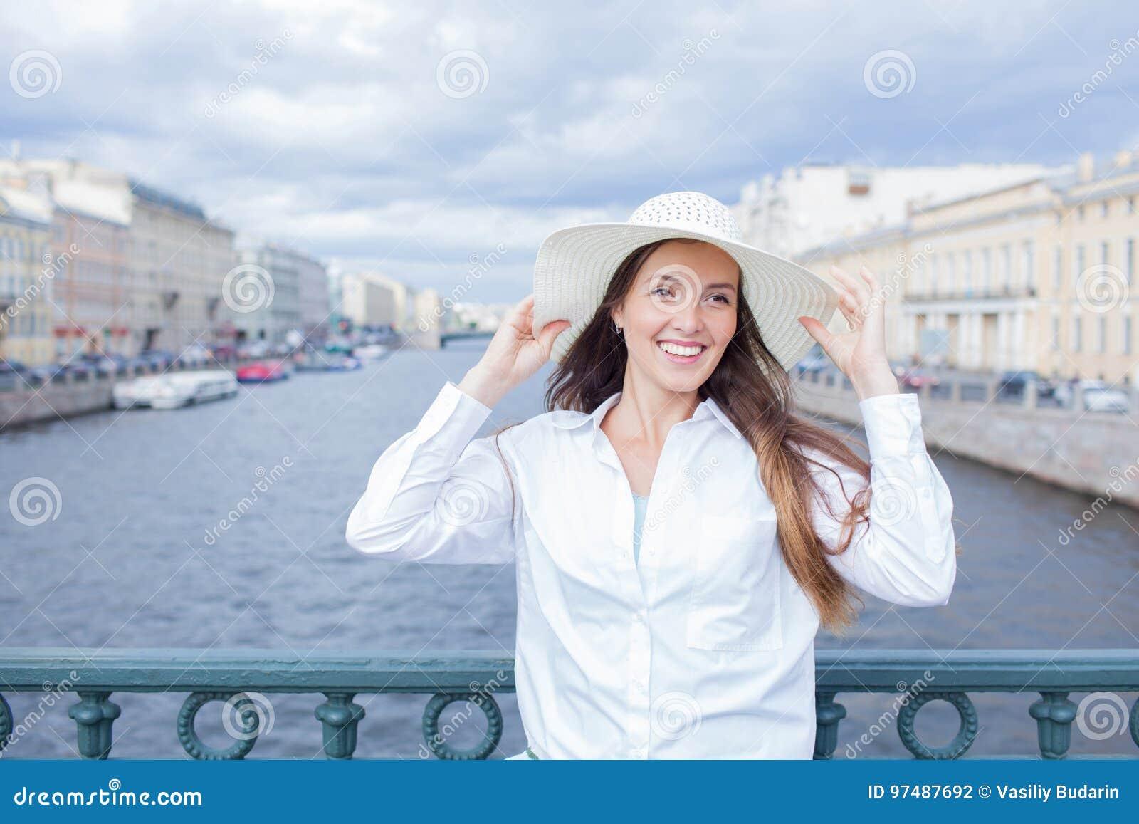 Una bella e ragazza sorridente in un cappello bianco con l ampio bordo sta stando sul ponte e sta parlando sul telefono contro il
