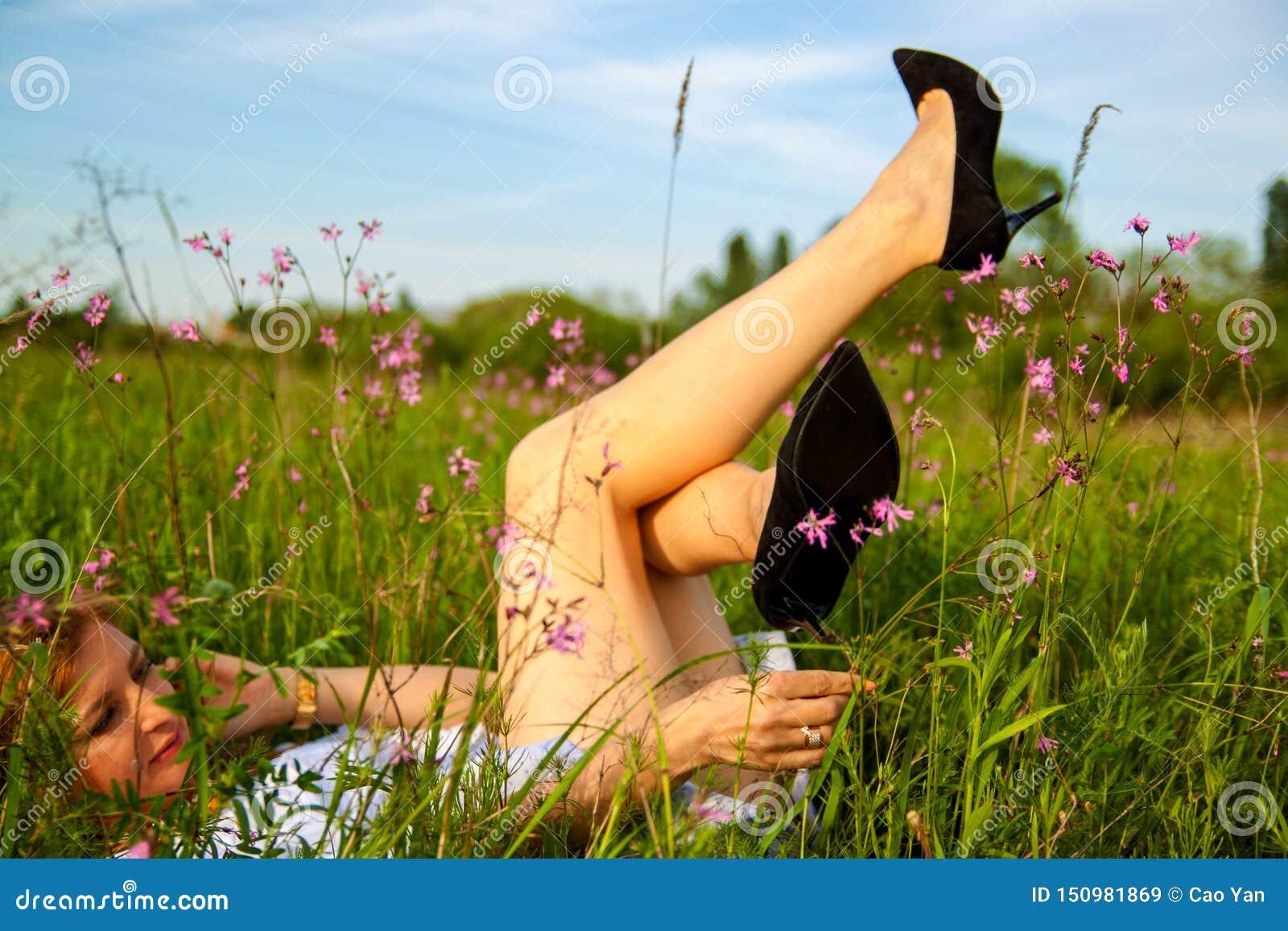 Una bella giovane donna che solleva i suoi vantaggi per il fondo dell erba verde