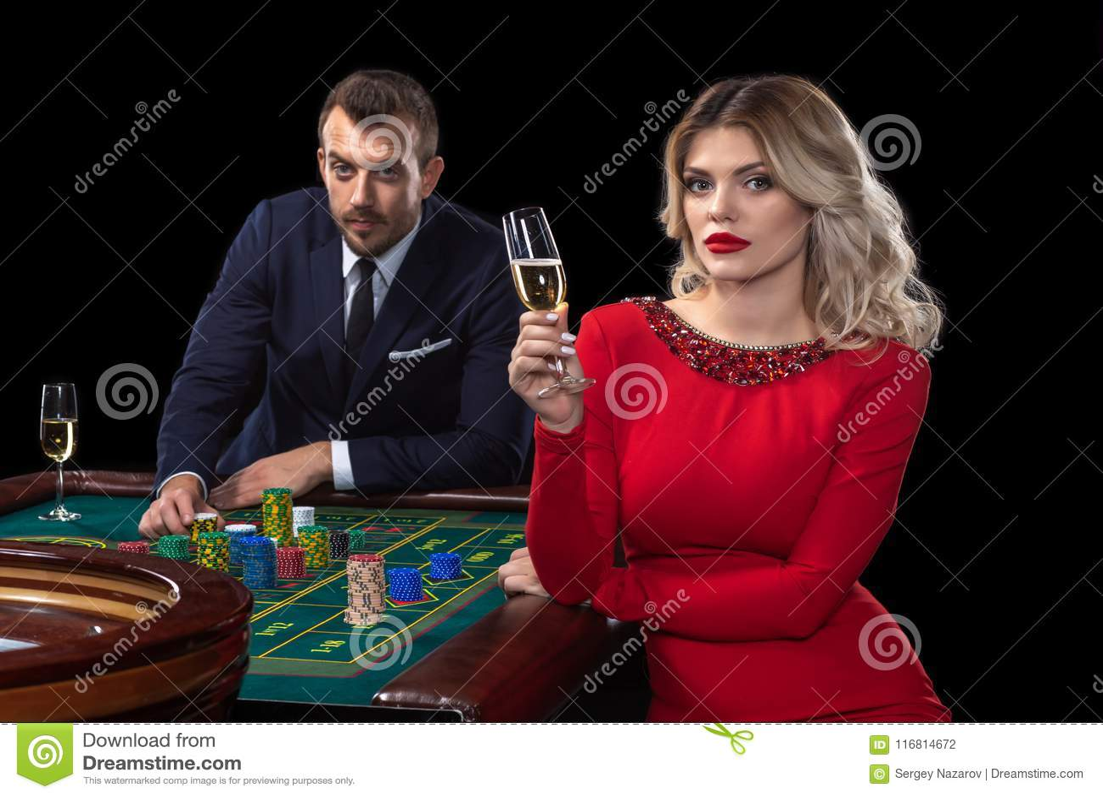 Una bella giovane donna e un uomo stanno sedendo ad una tavola delle roulette casino