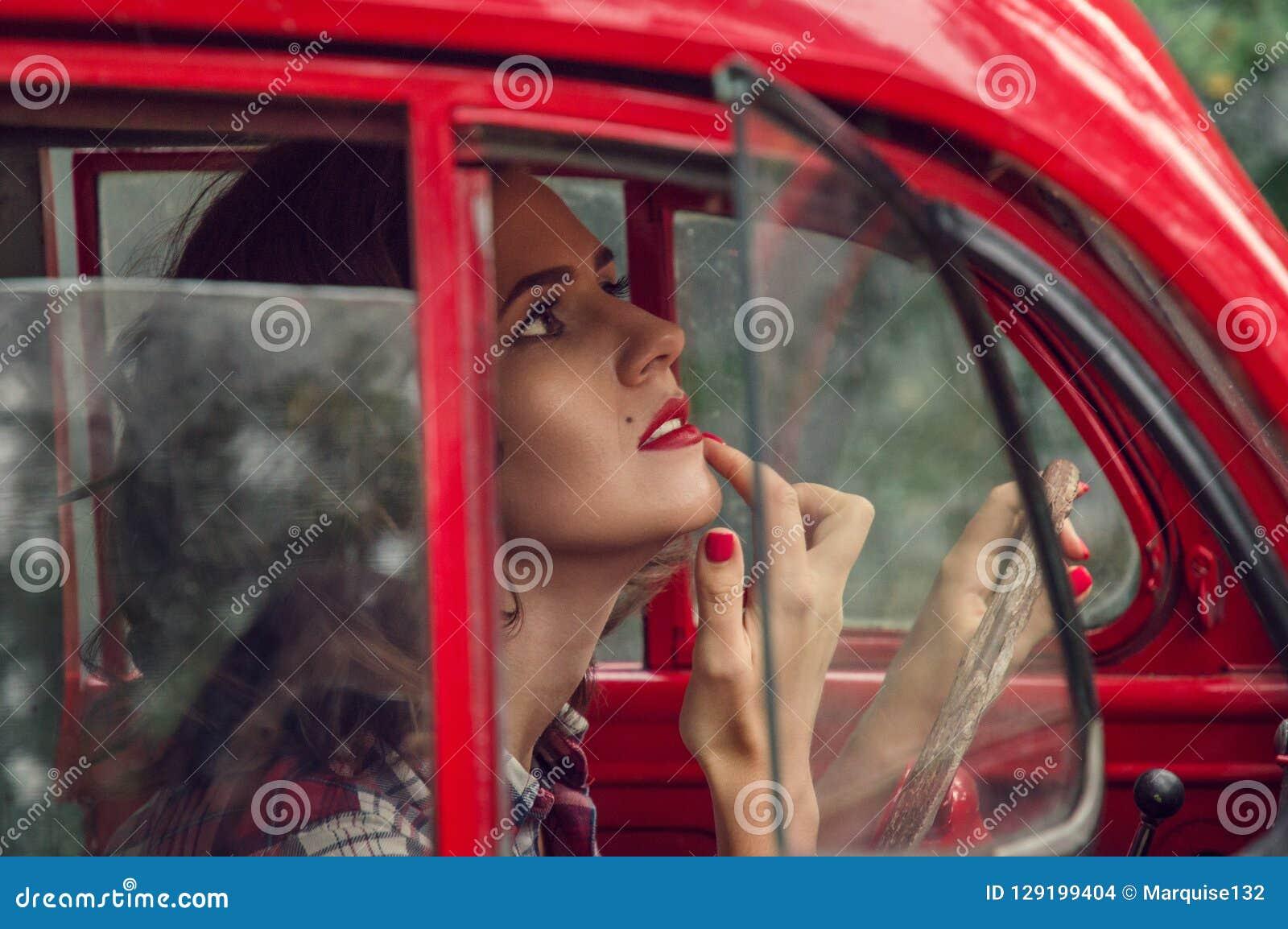 Una bella pin-up in una camicia di plaid corregge il trucco nel salone di vecchia retro automobile rossa
