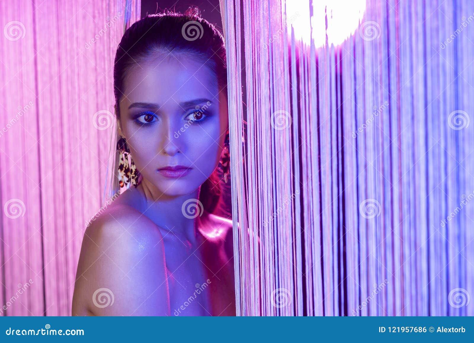 Una bella ragazza castana affascinante con l uso nudo delle spalle