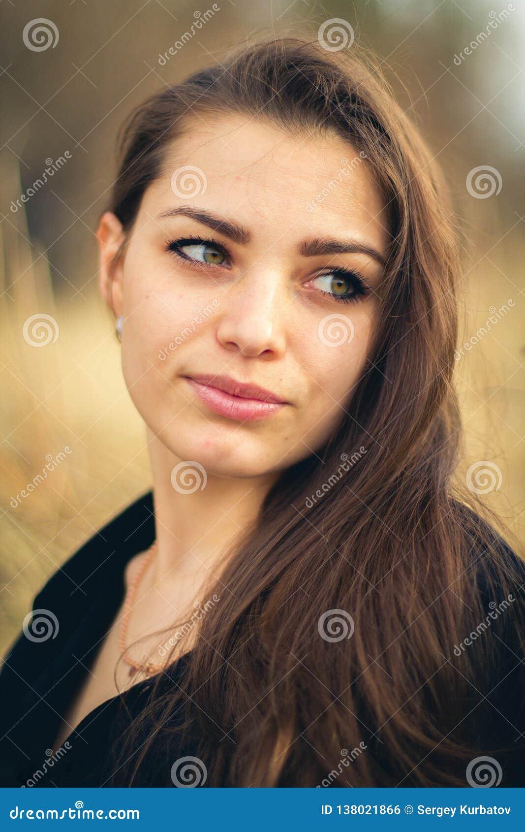 Una bella ragazza castana che posa in un campo sull autunno Foto di arte