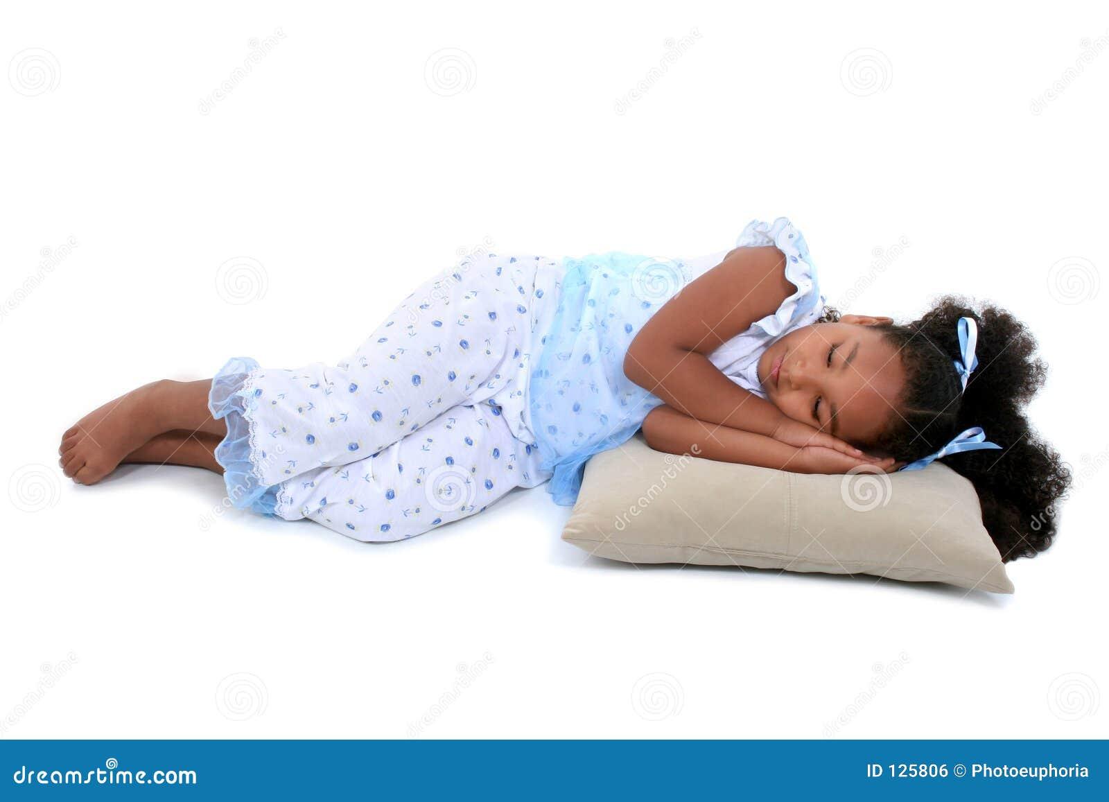 Una bella ragazza di sei anni che indica in pigiami sopra bianco