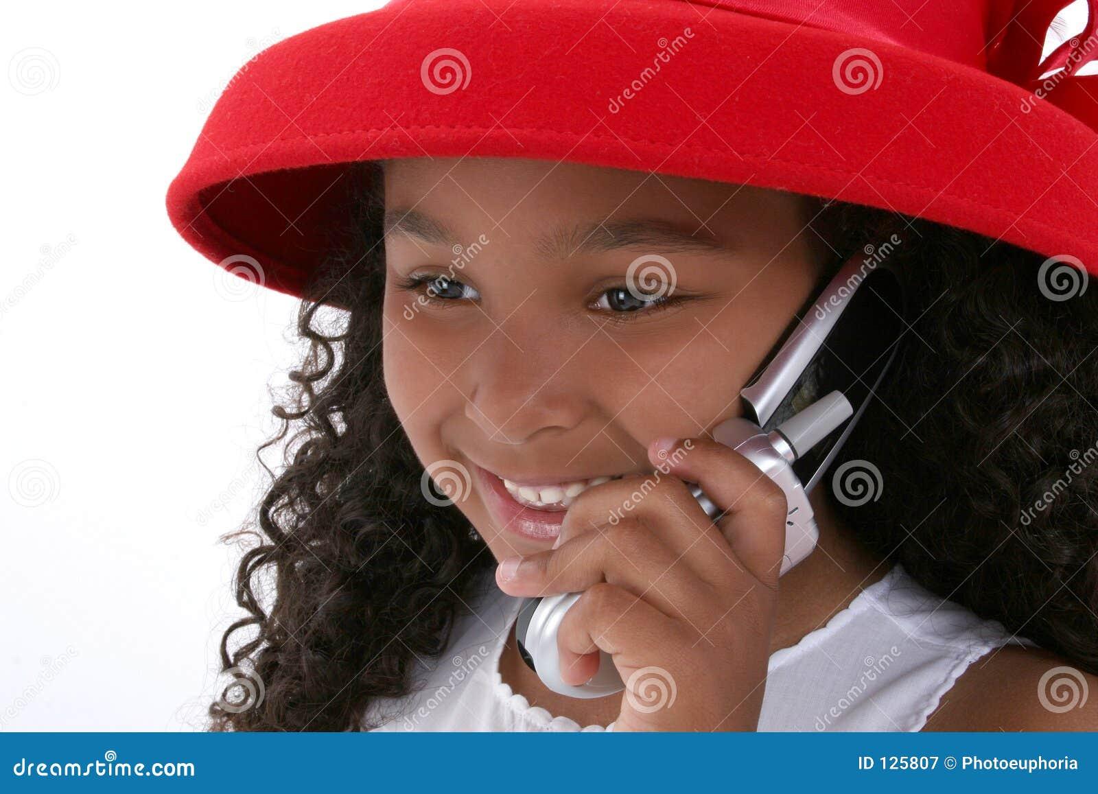 Una bella ragazza di sei anni in Red Hat con il cellulare