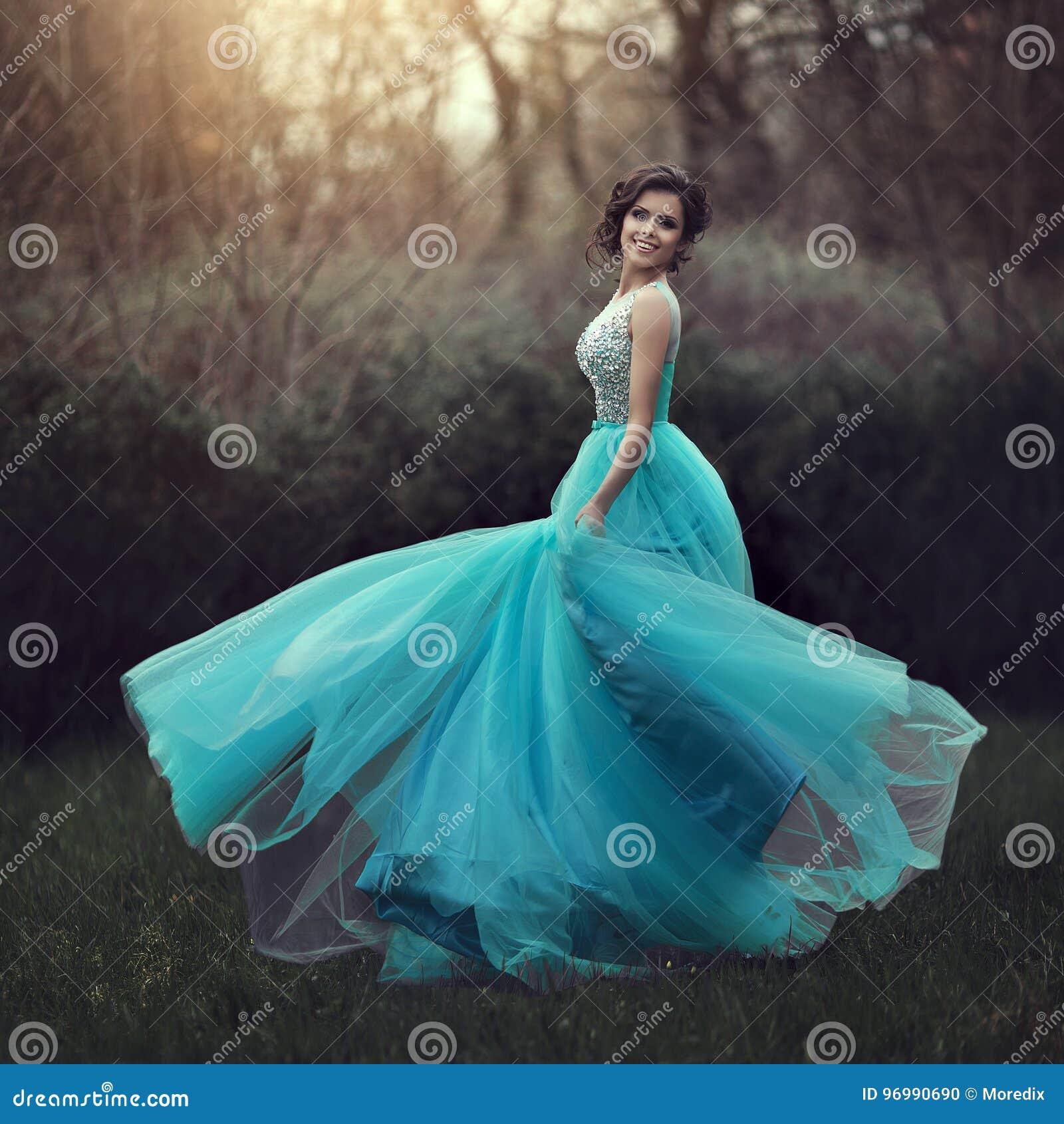 47b3671cd409 Una bella ragazza laureata sta filando in un vestito blu Giovane donna  elegante in un bello