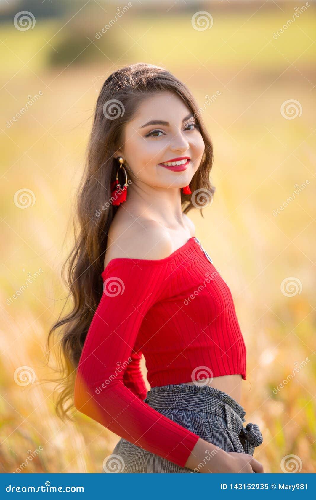 Una bella ragazza senior caucasica femminile della High School in maglione superiore del raccolto rosso