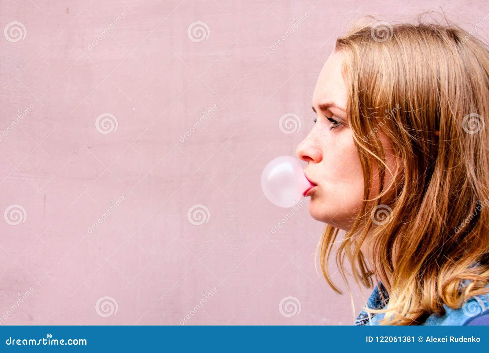 Una bella ragazza su un fondo di una tinta rosa sta nel profilo e soffia una palla di gomma da masticare