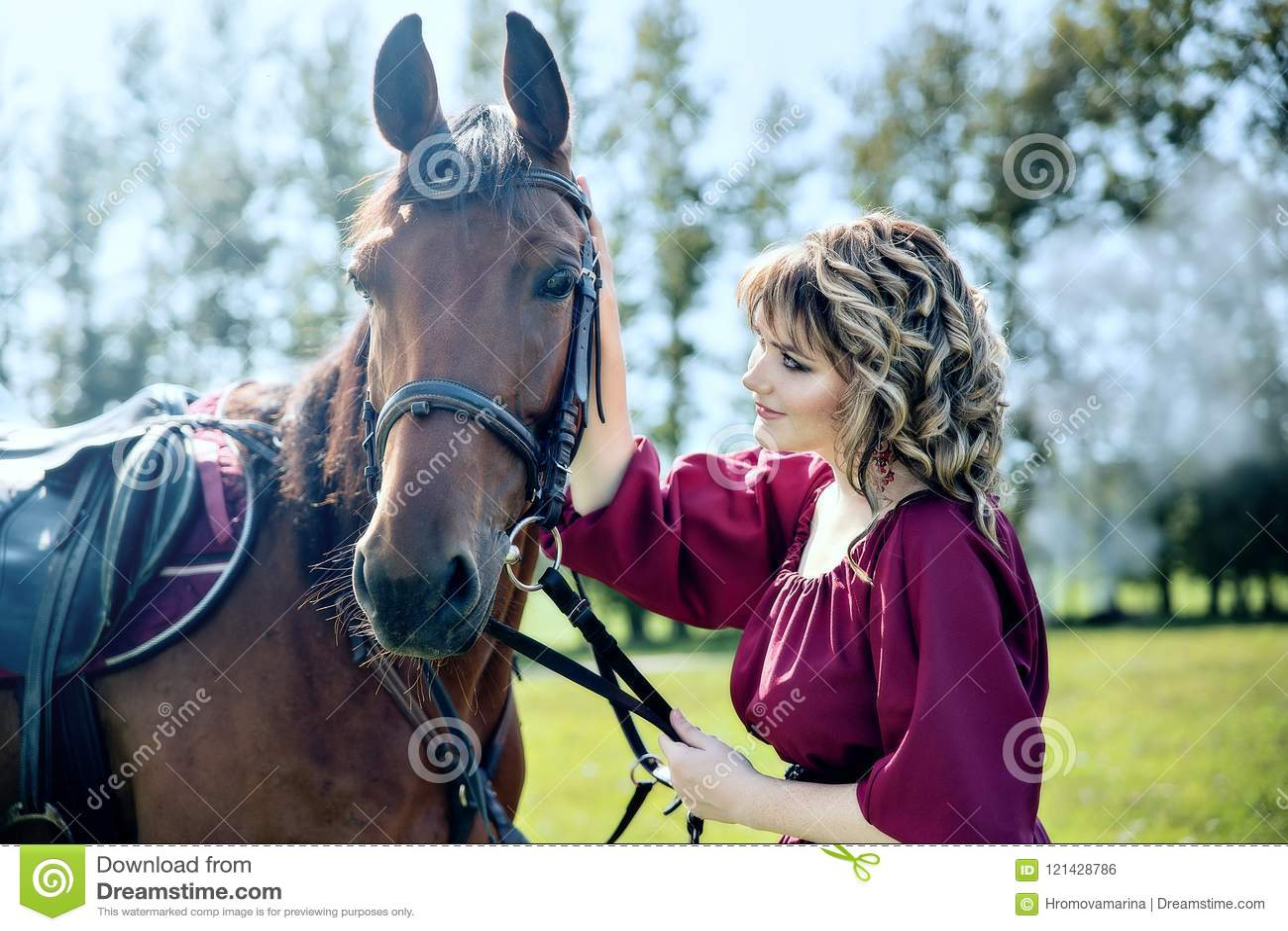 Una bella ragazza in un vestito da Borgogna ed in un cavallo marrone