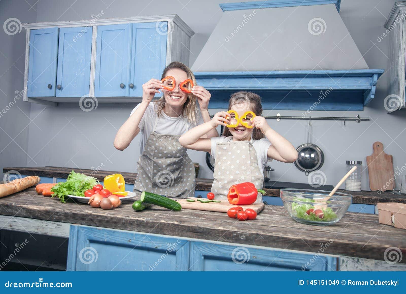 Una belle giovani madre e figlia si divertono la cottura di attimo