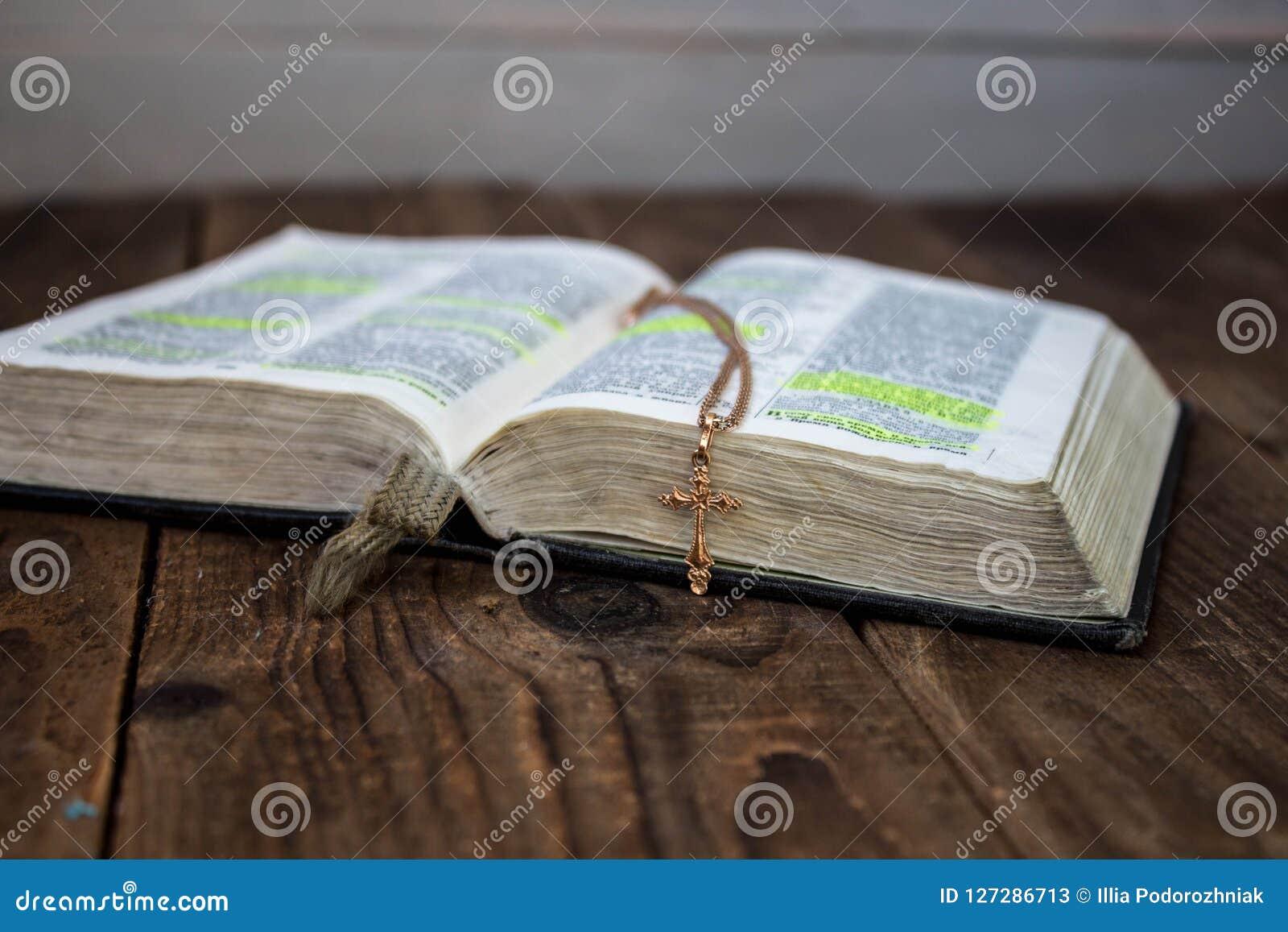 Una bibbia aperta e un incrocio dorato su fondo di legno