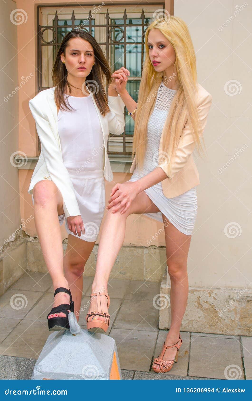 Una bionda di due amici e castana in vestiti bianchi che posano sulla via di vecchia città