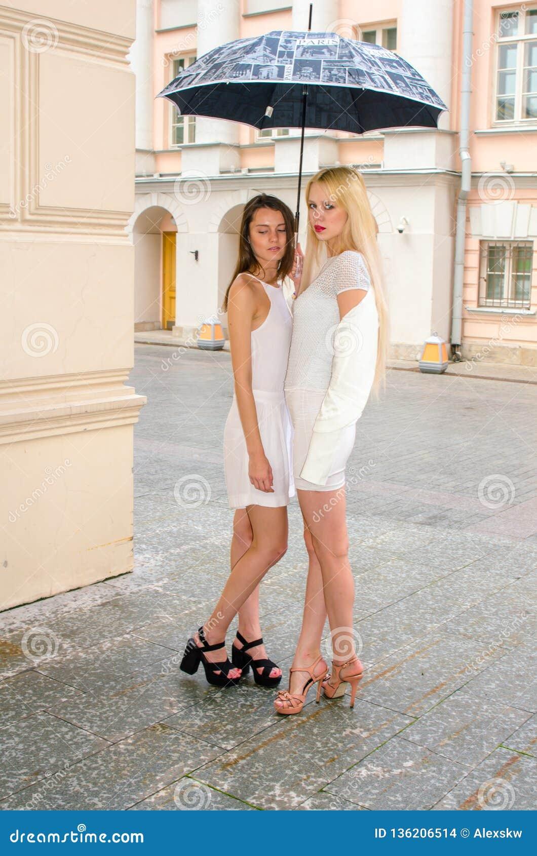 Una bionda di due amici e castana in vestiti bianchi che si nascondono dal tempo sotto un grande ombrello nei vicoli di vecchia c