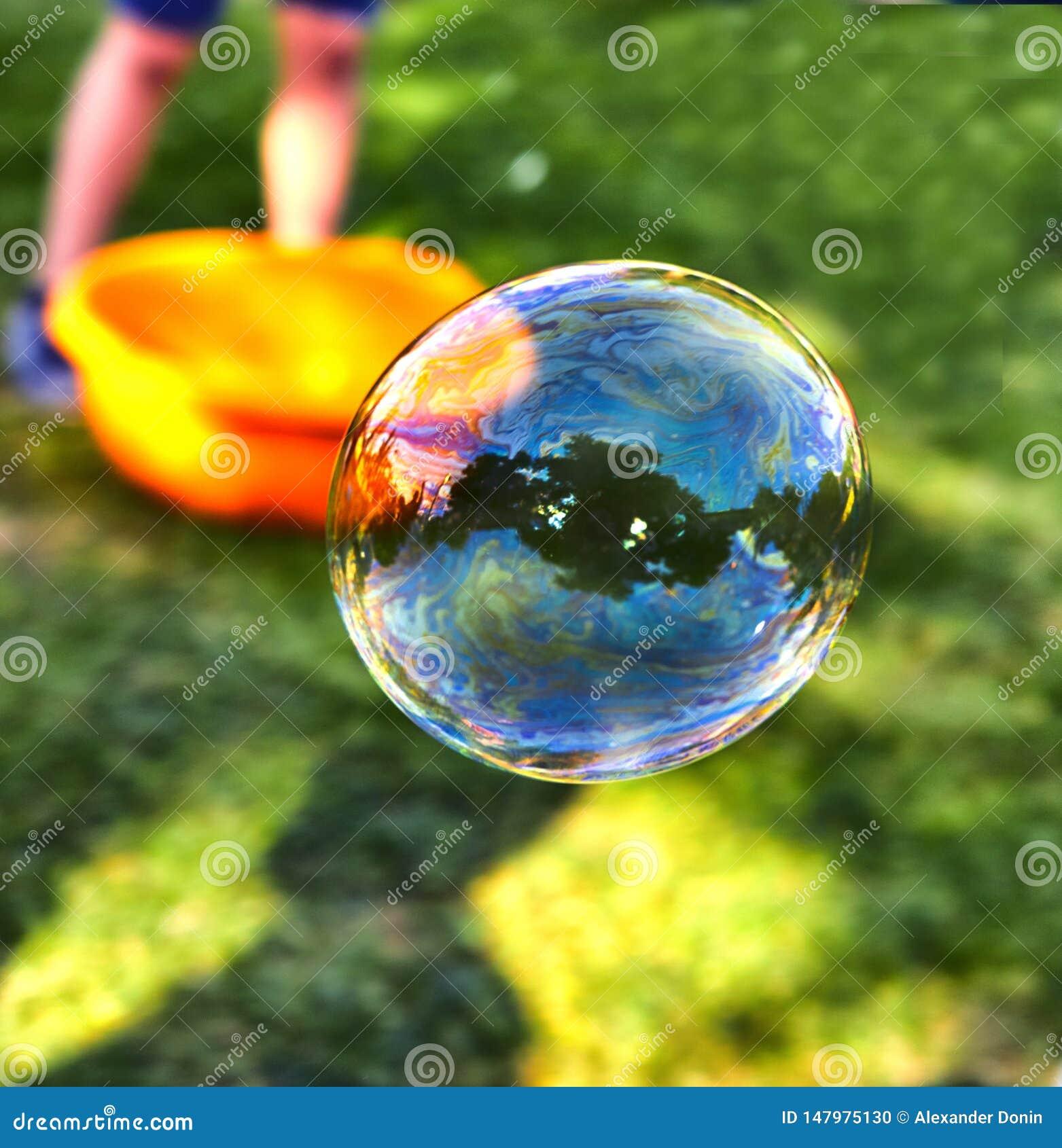 Una bolla di sapone vola contro lo sfondo di erba verde