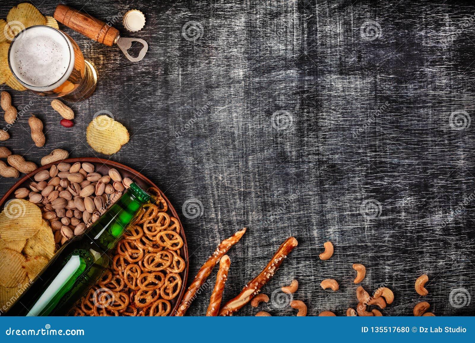 Una botella de cerveza en una placa con los pretzeles de los ookies, las nueces de pistacho y los microprocesadores salados en un