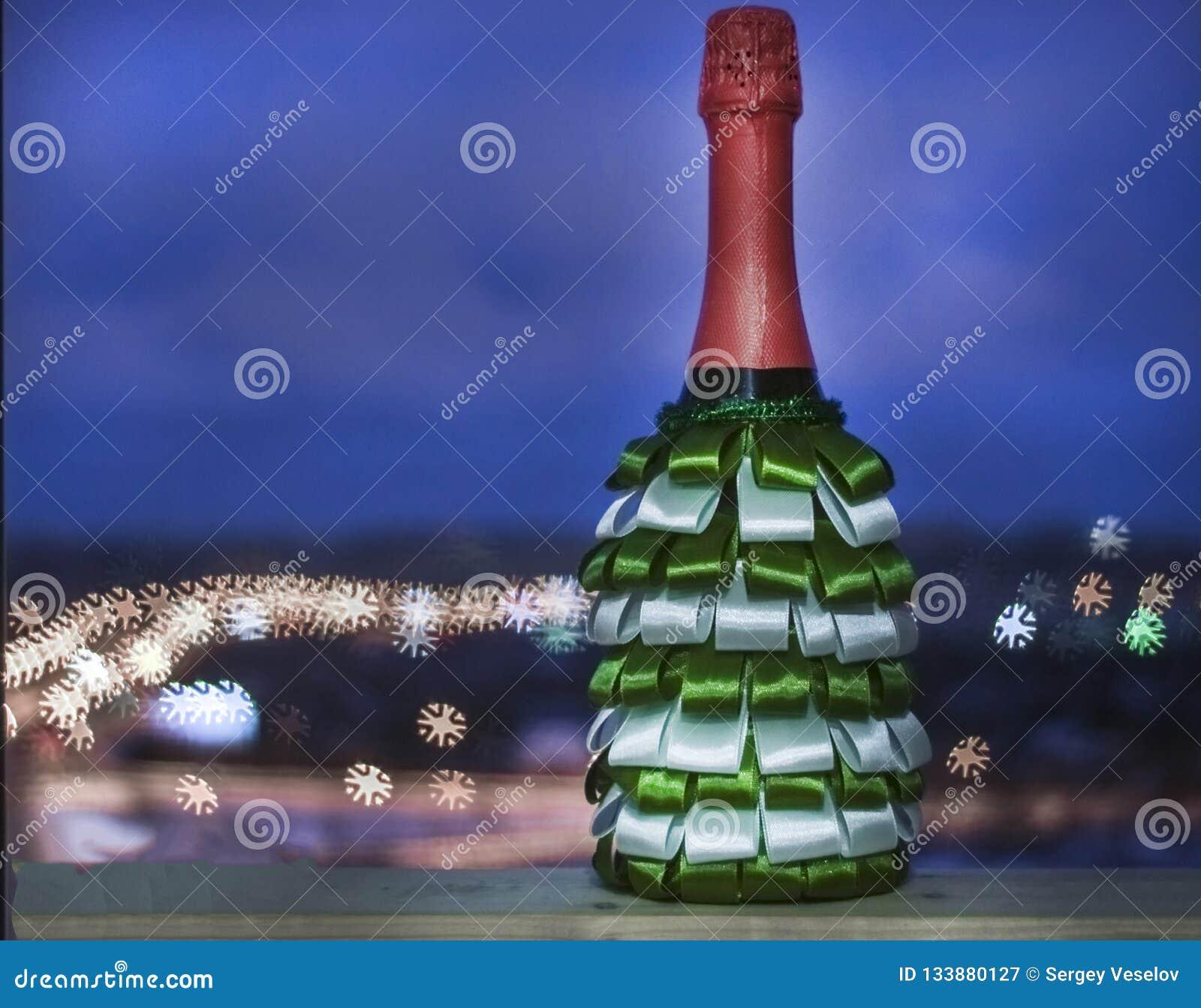 Una botella de champán adornada con las cintas de verde y de blanco