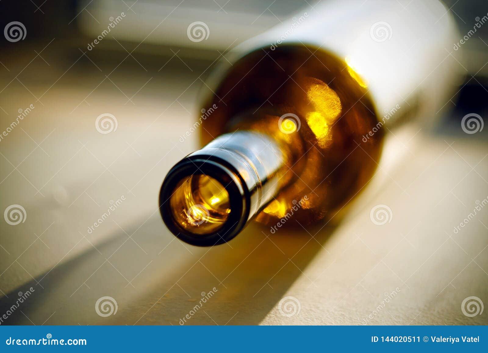 Una botella vacía de alcohol, miente en la superficie iluminada por el sol