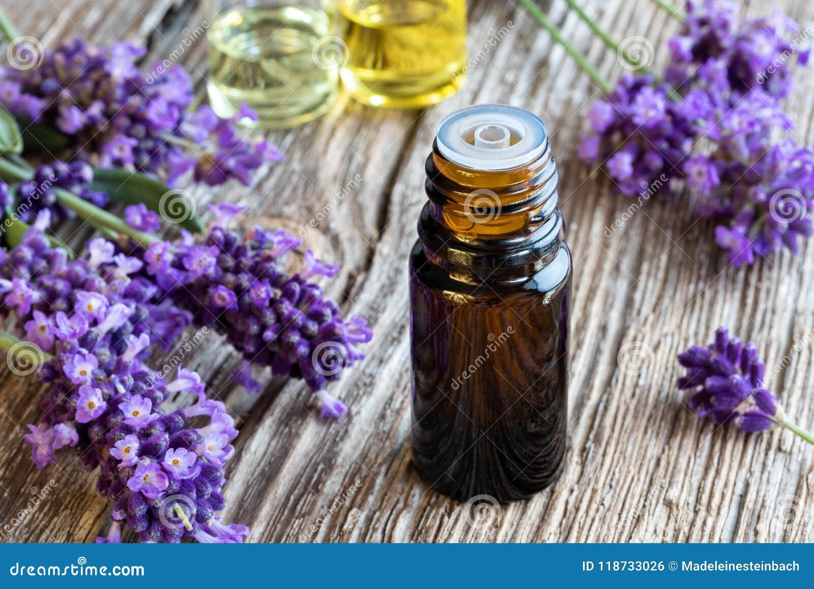 Una bottiglia dell olio essenziale della lavanda con lavanda di fioritura fresca