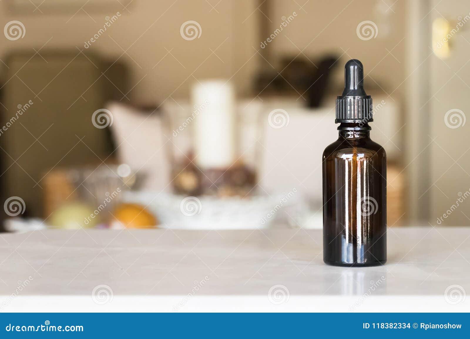Una bottiglia della medicina con il contagoccia sopra un fondo della sfuocatura della casa