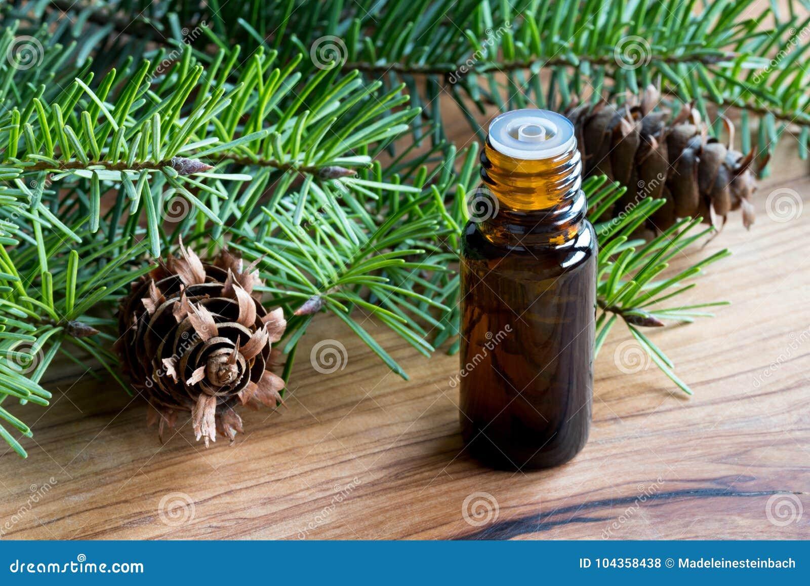 Una bottiglia scura dell olio essenziale dell abete di douglas con la crusca dell abete di douglas