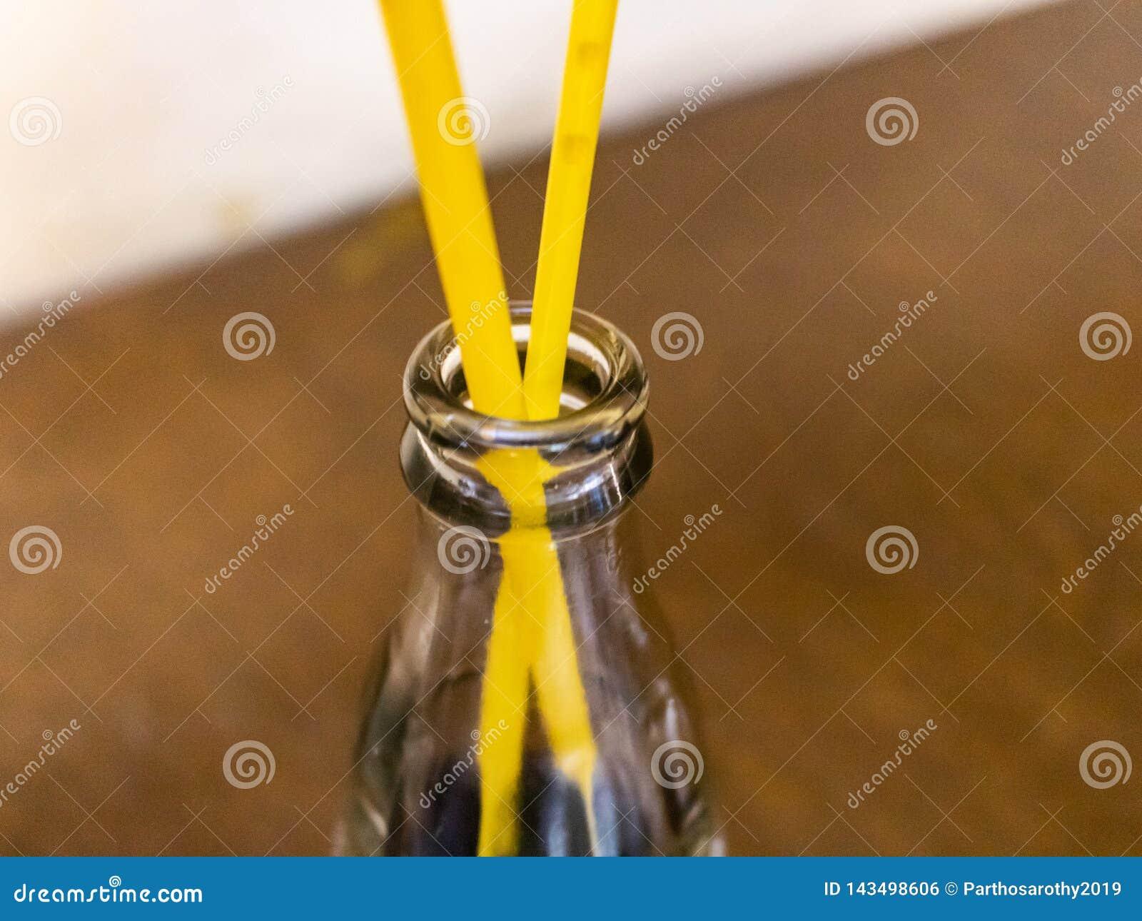 Una bottiglia vuota con i tubi beventi in un ristorante