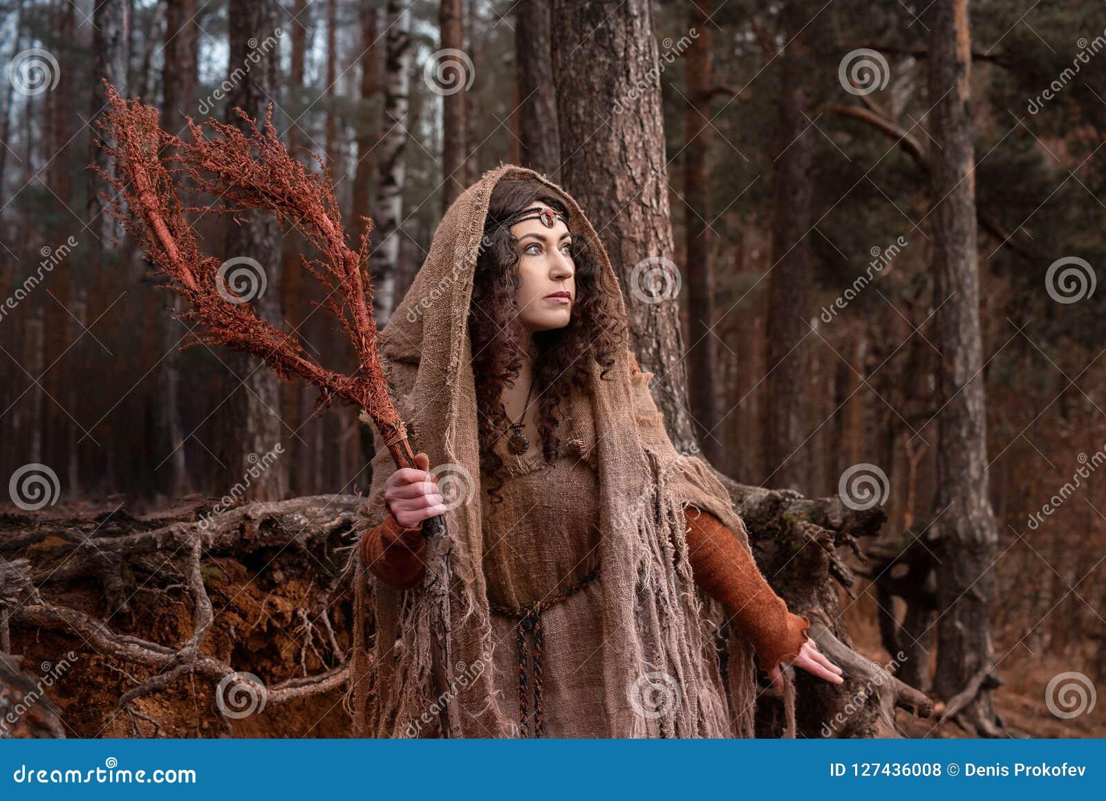 Una bruja en trapos conjura en bosque