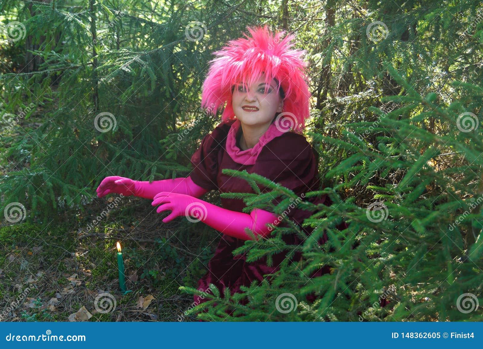 Una bruja joven en ropa púrpura conjura una vela cavada en la tierra Foto horizontal