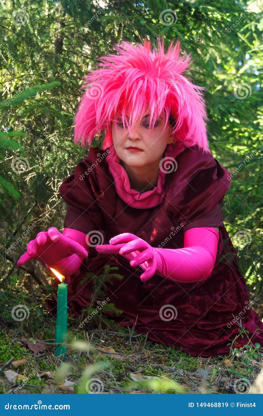 Una bruja joven en ropa p?rpura conjura una vela cavada en la tierra