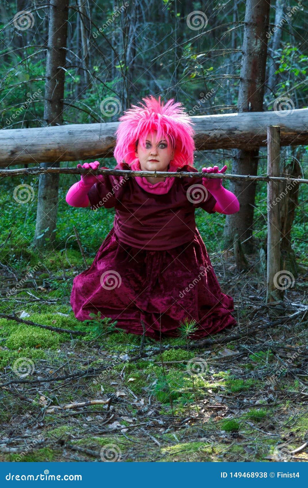 Una bruja joven en ropa p?rpura en el bosque conjura una rama seca de un ?rbol