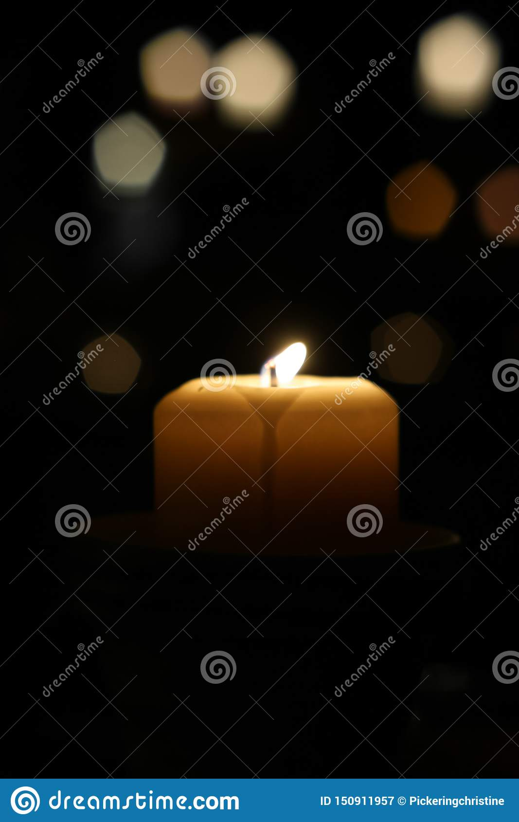 Una candela tremola brillantemente su una notte scura