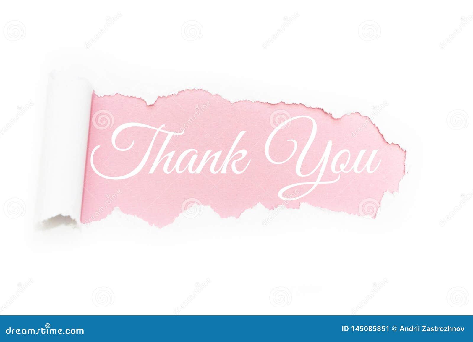Una carta de agradecimiento capital en la ruptura del documento sobre un fondo rosado