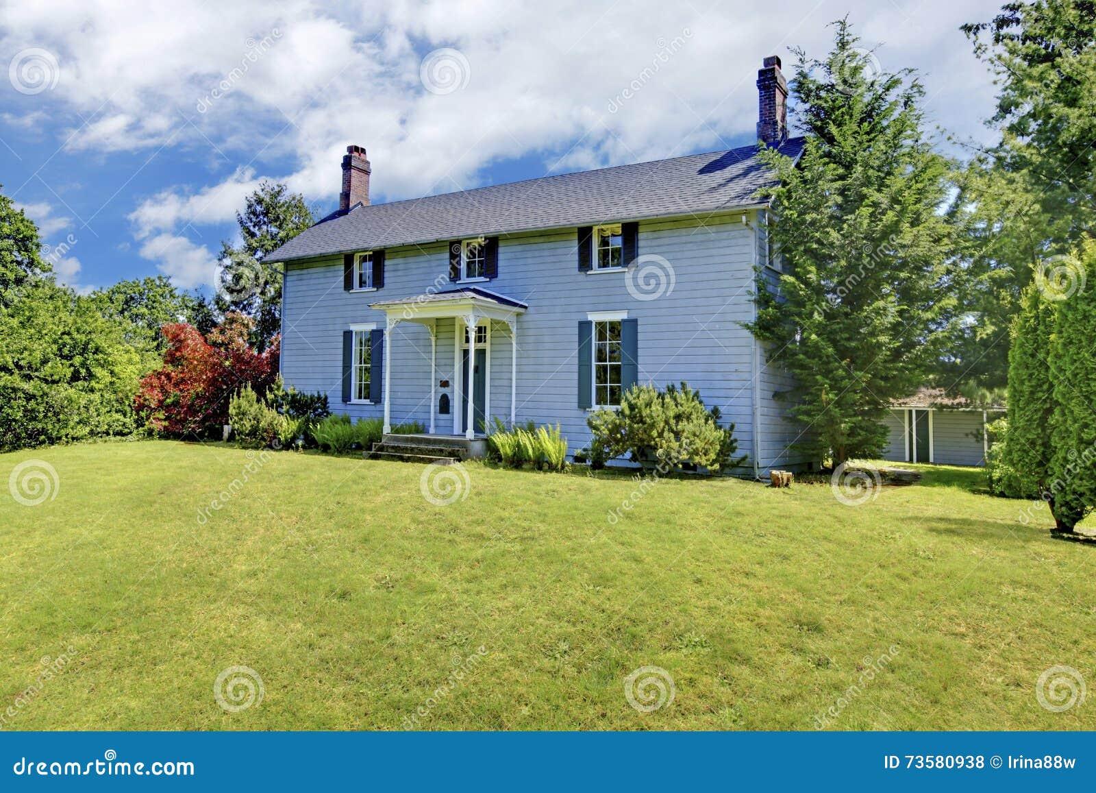 Una casa di due storie con pittura per esterni blu ed il for Una casa di tronchi con garage