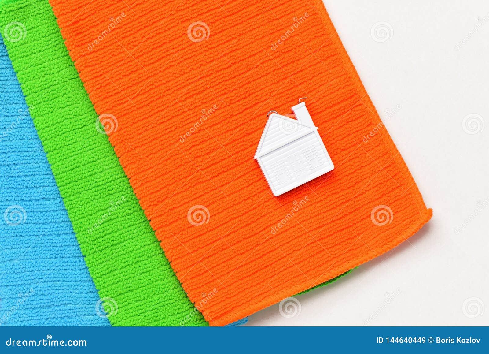 Una casetta si trova su una pila di tre asciugamani su un fondo bianco