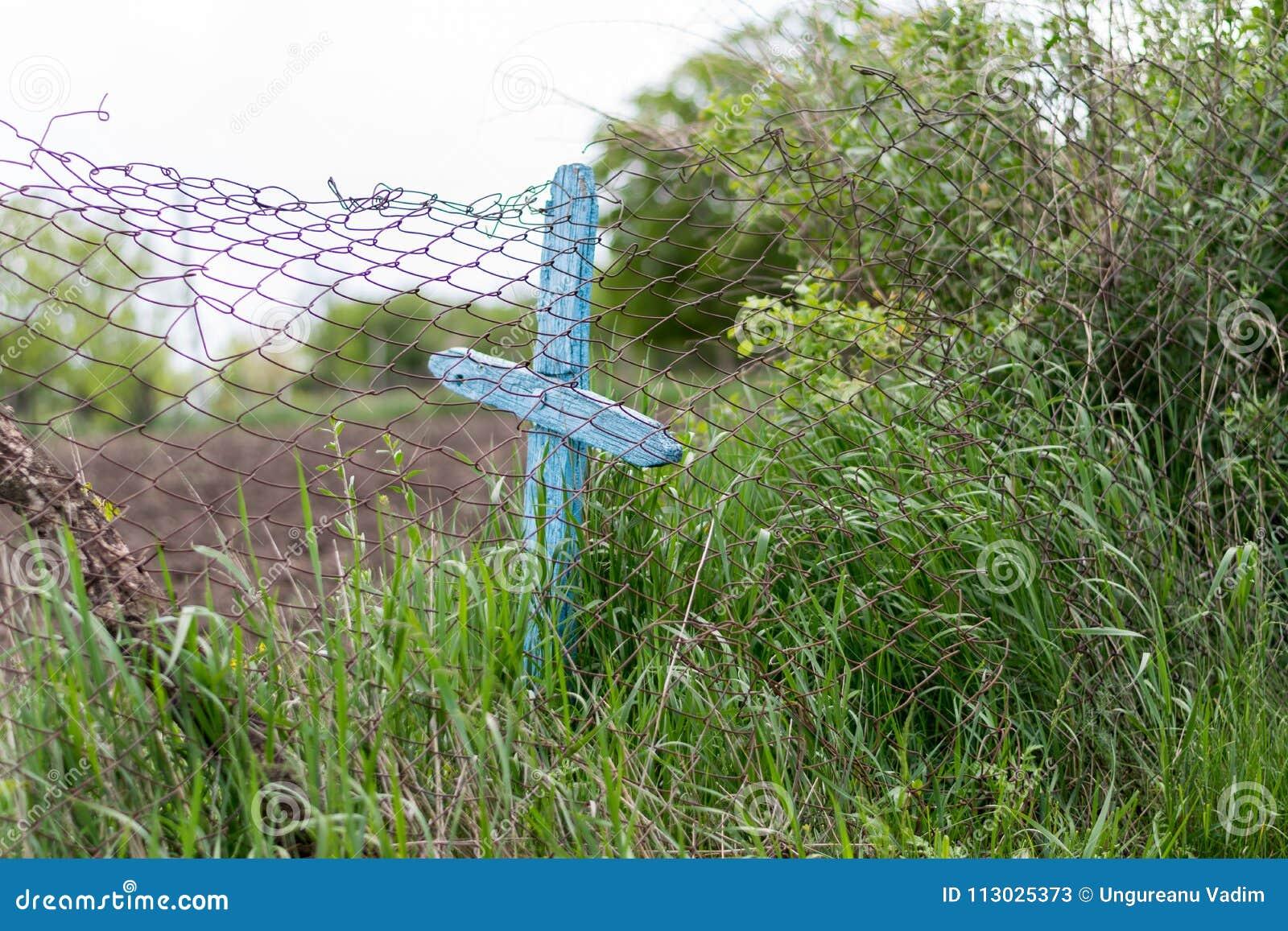 Una cerca con una cruz azul que la para caer