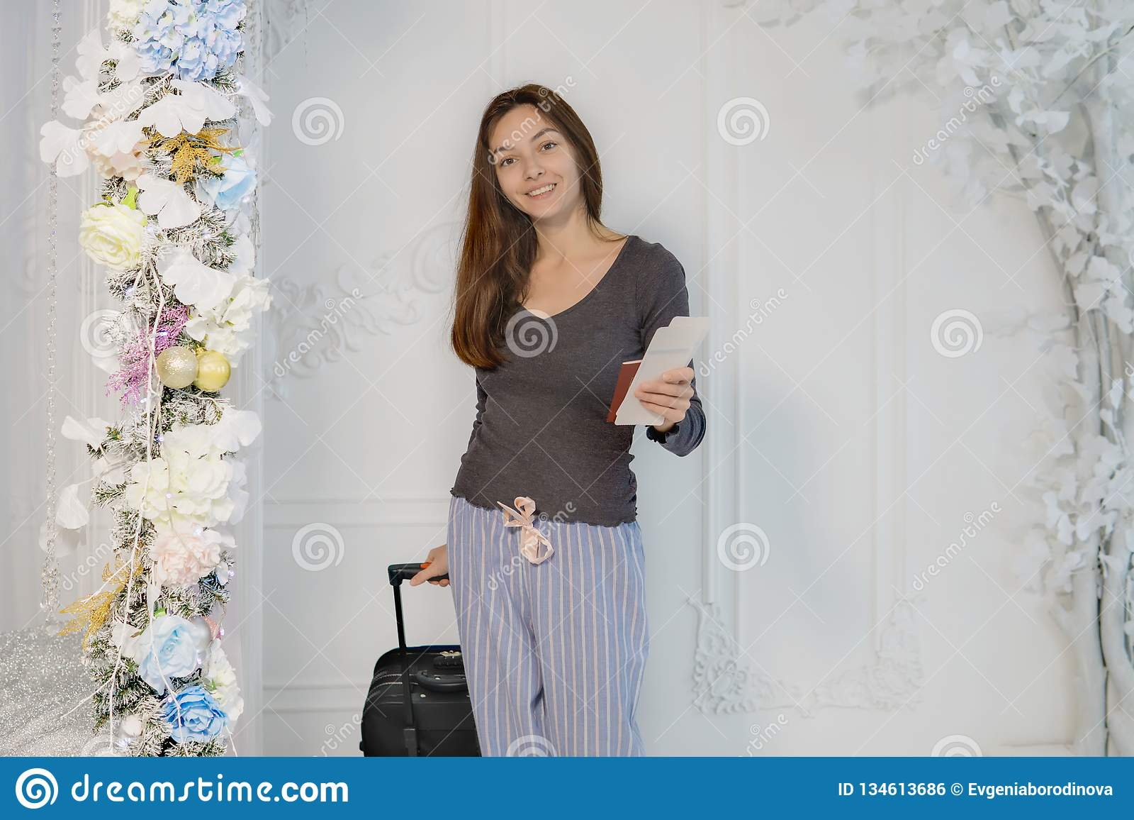 Una chica joven en una chaqueta marrón con los boletos y un pasaporte en sus manos mira la cámara, sonríe, lleva una maleta