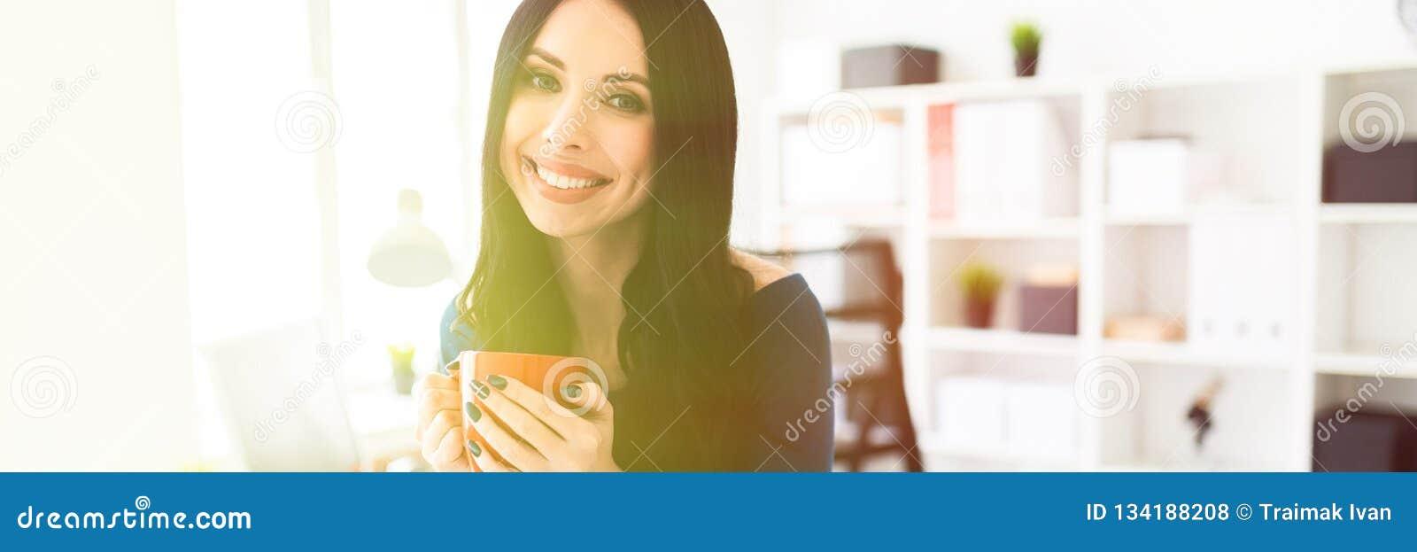 Una chica joven en la oficina sentada abajo en la tabla y sostenía una taza roja en sus manos