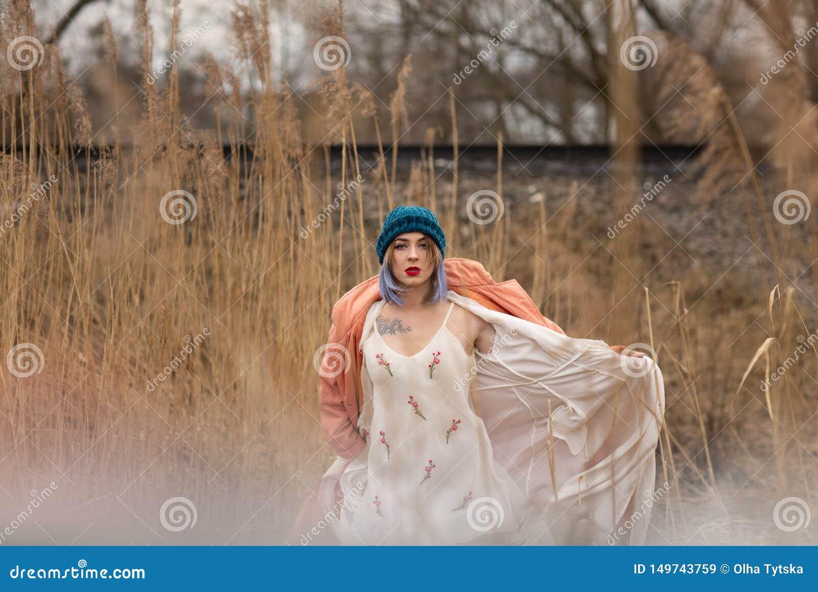 Una chica joven en un vestido blanco hermoso y un sombrero elegante presenta en un campo de trigo