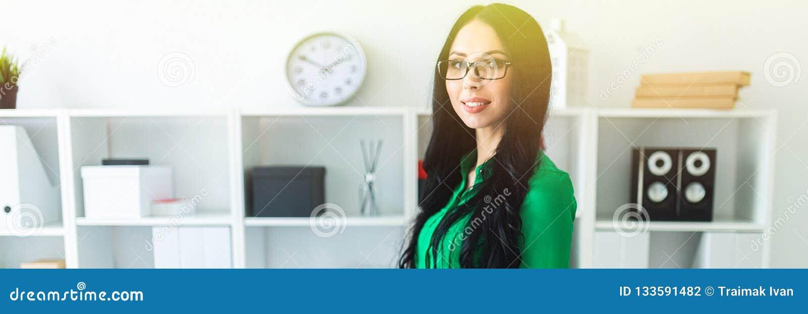 Una chica joven en vidrios se coloca en la oficina y pone sus manos en la parte de atrás de la silla