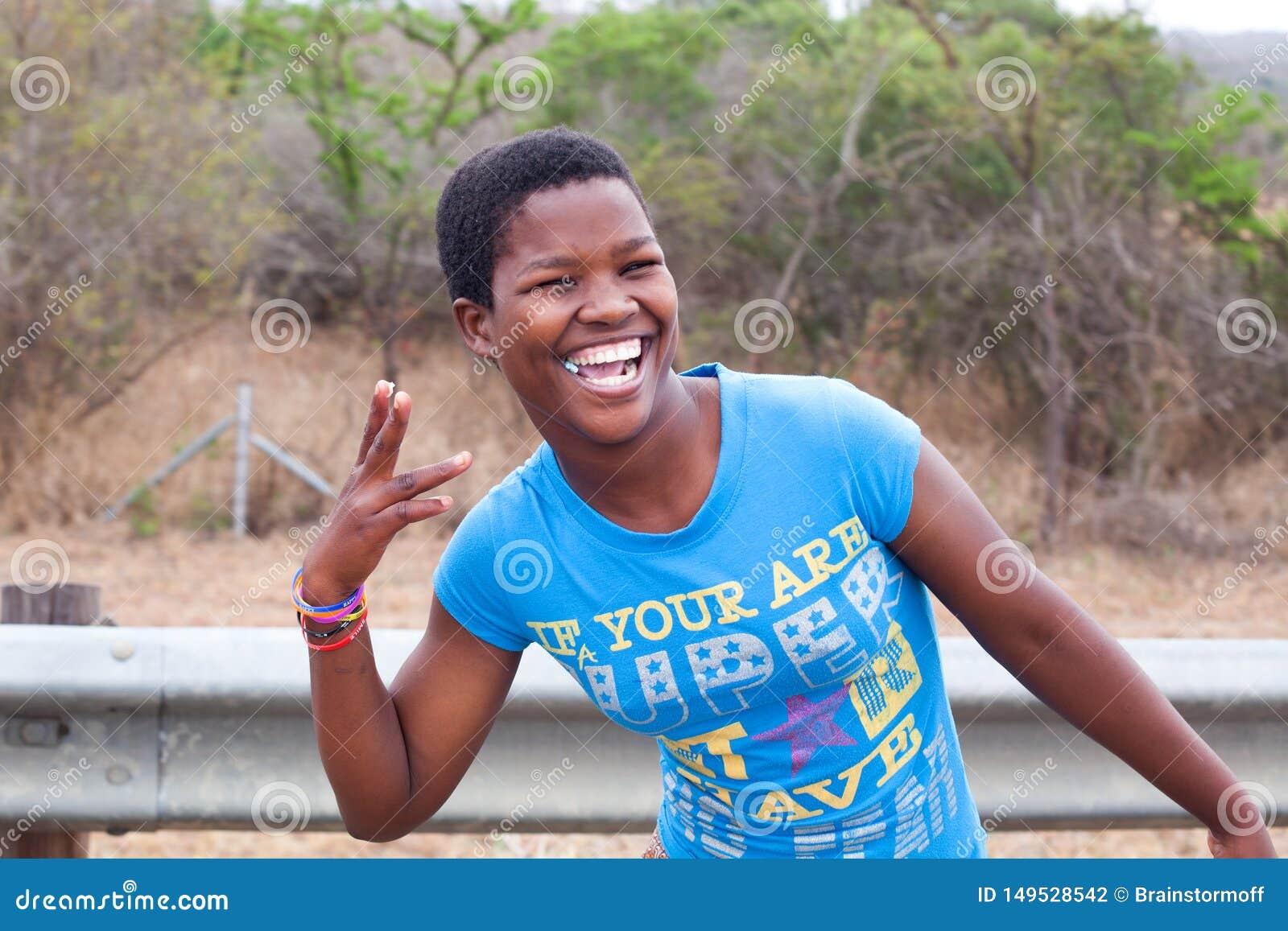 Una chica joven hermosa africana feliz en camiseta azul que sonr?e con los dientes blancos y el chicle al aire libre cercanos par