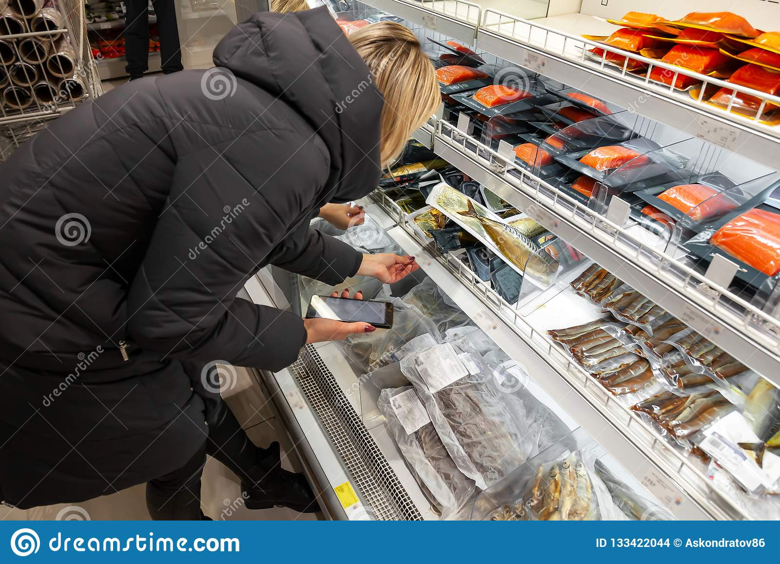 Una chica joven rubia en una chaqueta larga elige compras del rato de la comida