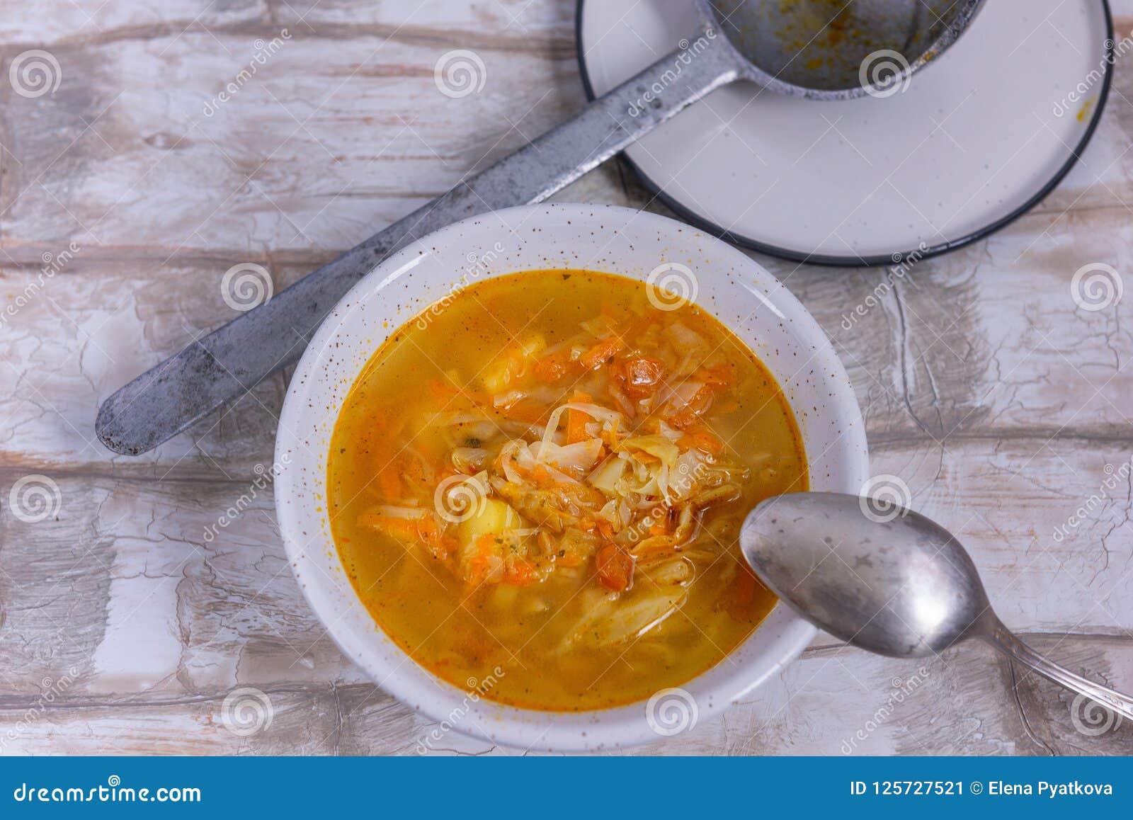 Una ciotola di minestra con una vecchia siviera della latta di Selenin