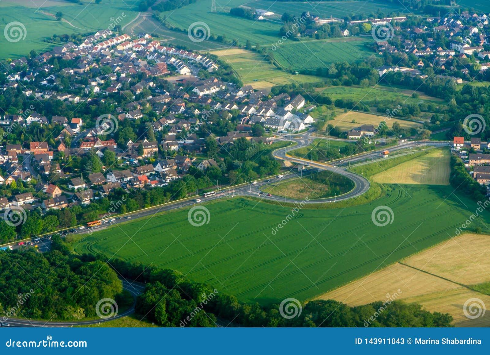 Una ciudad con las casas bajas rodeadas por la carretera la visión desde arriba de la troposfera