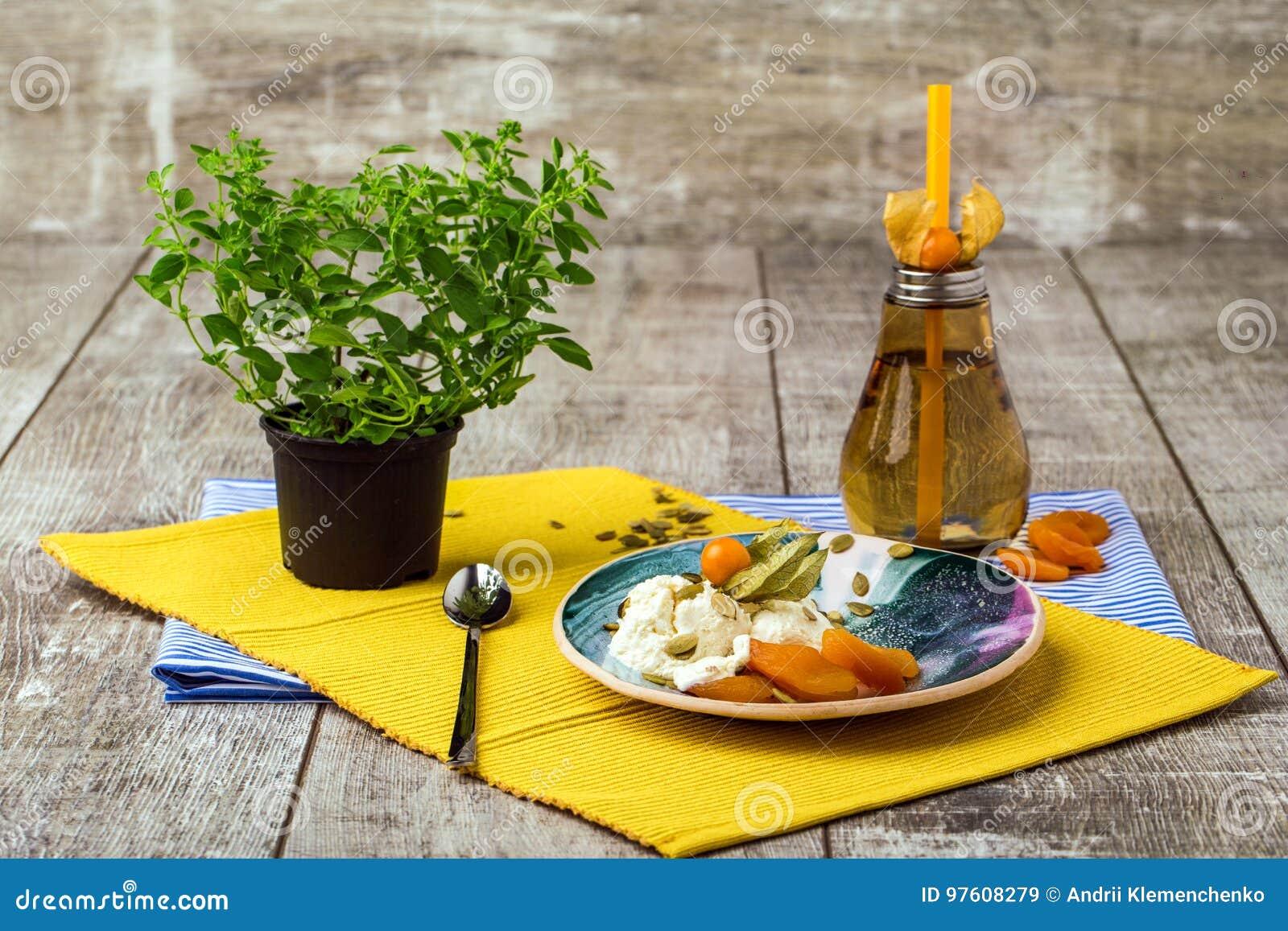 Una composición brillante de una placa redonda, de una botella anaranjada, y de un árbol chino verde Un sistema de cena lindo en