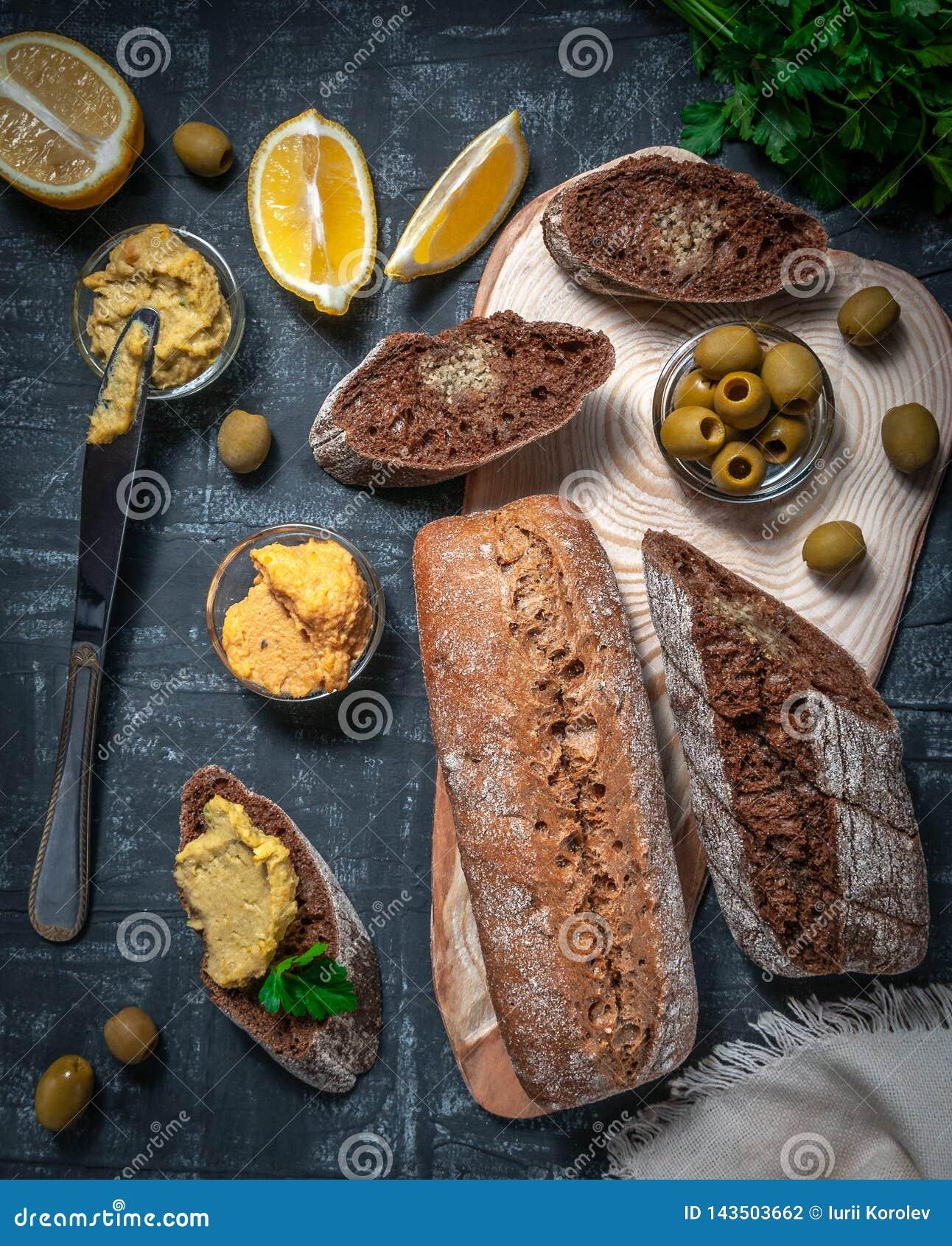 Una composición de dos baguettes de salvado y de harina entera del grano Bocadillo del hummus y de aceitunas En el espaciamiento