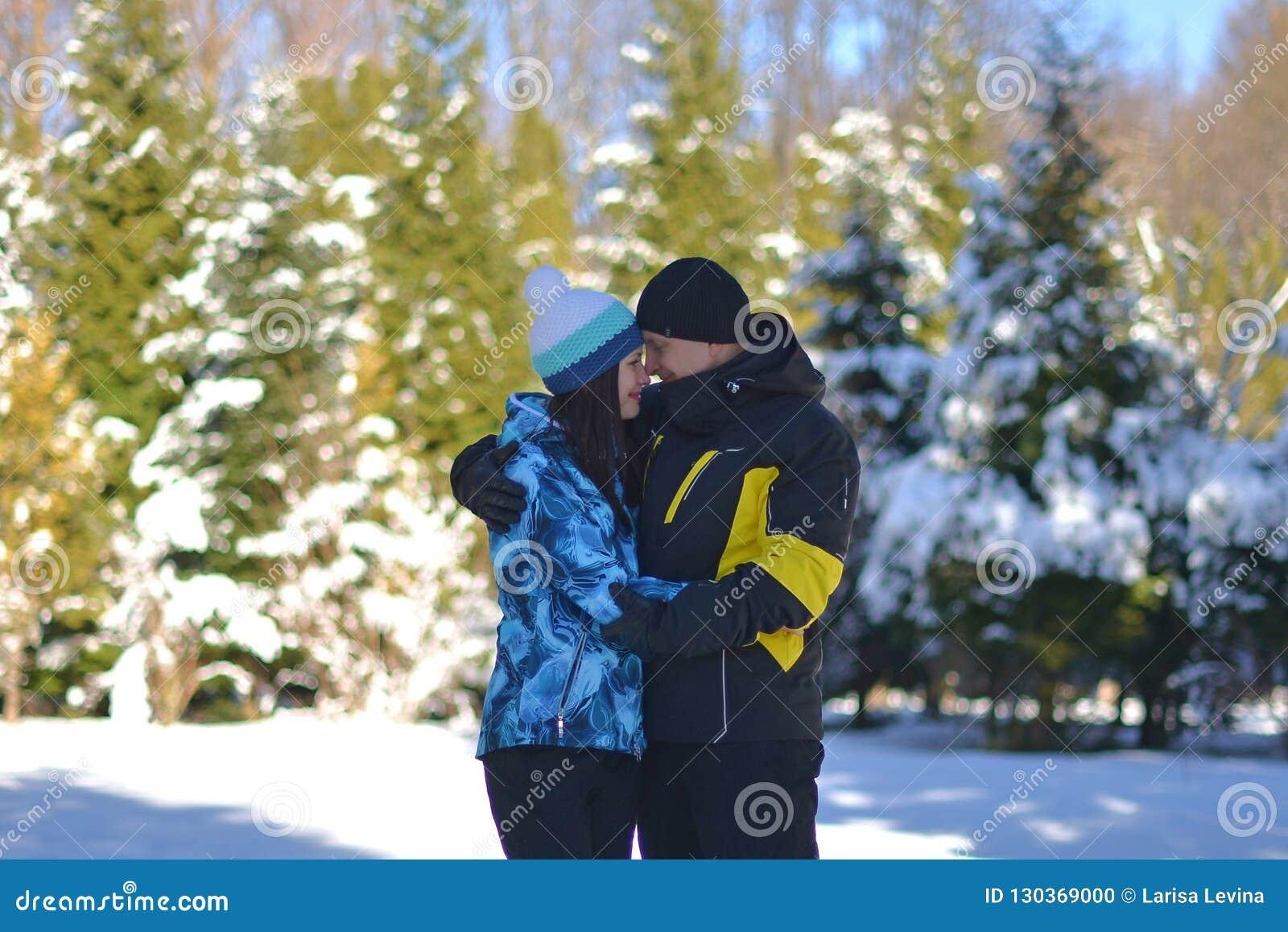 Una coppia amorosa sposata che imbroglia intorno in una foresta nevosa su un inverno soleggiato