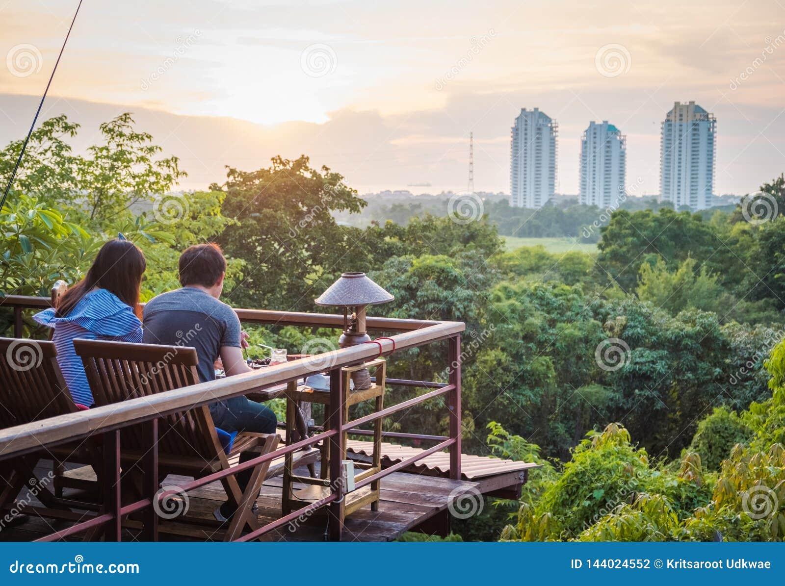 Una coppia che dinning davanti alla foresta ed alle costruzioni