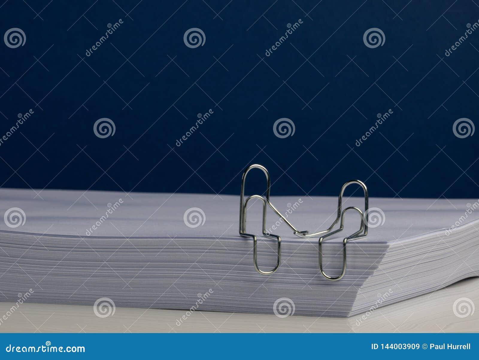 Una coppia del carattere della graffetta che si tiene per mano sulla risma di carta